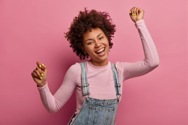 Vrolijke donkere huid afrikaans-amerikaans vrouwelijk model danst en voelt zich vrolijk, draagt coltrui en denim sarafan, lacht breed, heeft plezier en beweegt met het ritme van muziek, geïsoleerd over roze muur