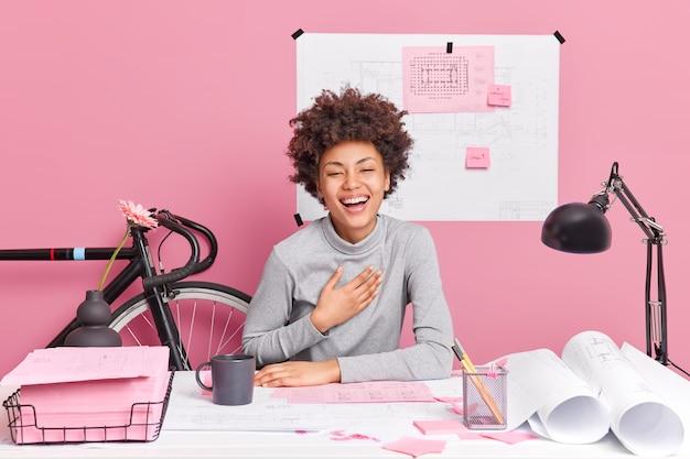 Vrolijke, donkere huid geïnspireerde vrouwelijke ontwerpmedewerker giechelt vrolijk zit op de werkplek maakt tekeningen drukt positieve emoties uit geniet van haar beroep bestudeert technische blauwdrukken op desktop