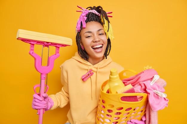 Vrolijke donkere huishoudster glimlacht breed draagt sweatshirt en beschermende rubberen handschoenen houdt wasmand en dweil blij om huishoudelijk werk geïsoleerd op geel af te maken