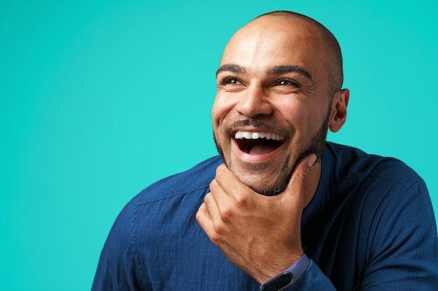 Vrolijke donkere man lachend op turkoois
