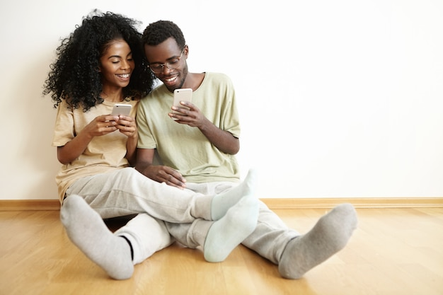 Vrolijke donkere paar genieten van online communicatie, videospelletjes spelen op mobiele telefoons. man in glazen iets op internet tonen aan zijn vriendin