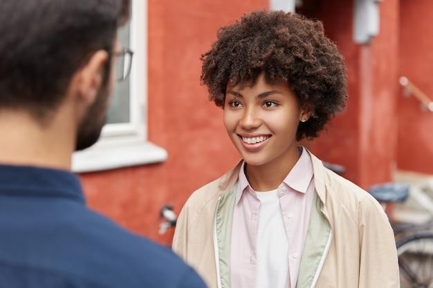 Vrolijke donkere vrouw met brede glimlach, draagt casual jas