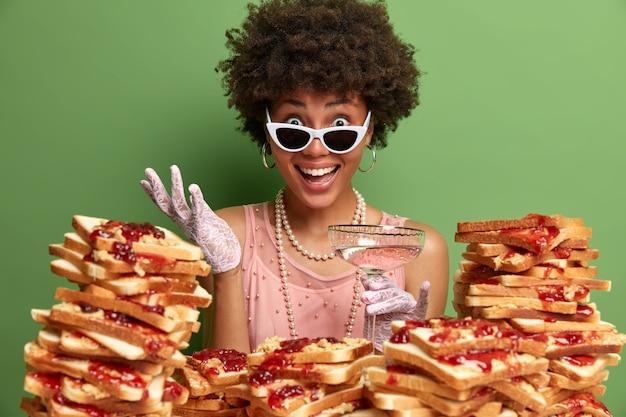 Vrolijke donkere vrouw met krullend haar, gekleed in stijlvolle kleding, draagt een zonnebril, drinkt een alcoholische cocktail, hoort uitstekend nieuws van de gesprekspartner, staat in de buurt van stapel sandwiches.
