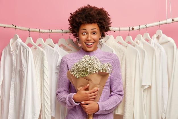 Vrolijke donkere vrouw vormt in kleedkamer met boeket, draagt paarse trui, witte kleren op hangers op achtergrond, kijkt met een brede glimlach naar de camera.