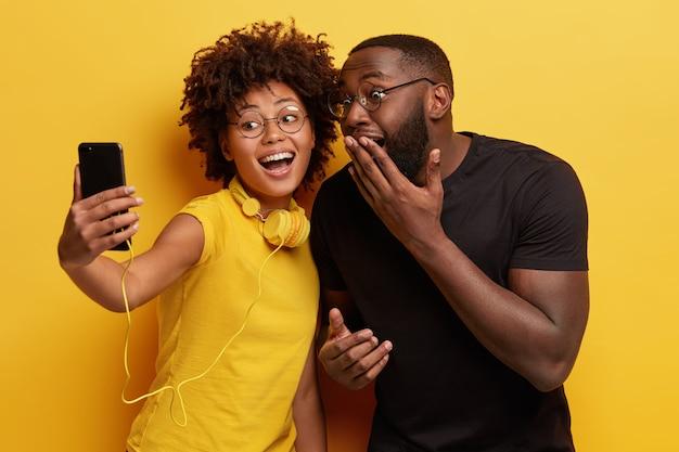 Vrolijke, donkere vrouwelijke en mannelijke paar hebben samen plezier, poseren voor het maken van een selfie-portret