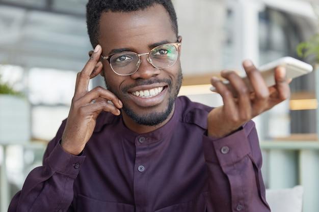 Vrolijke donkere welvarende zakenman in bril, heeft een brede stralende glimlach, houdt slimme telefoon vast en bevestigt bankieren in app