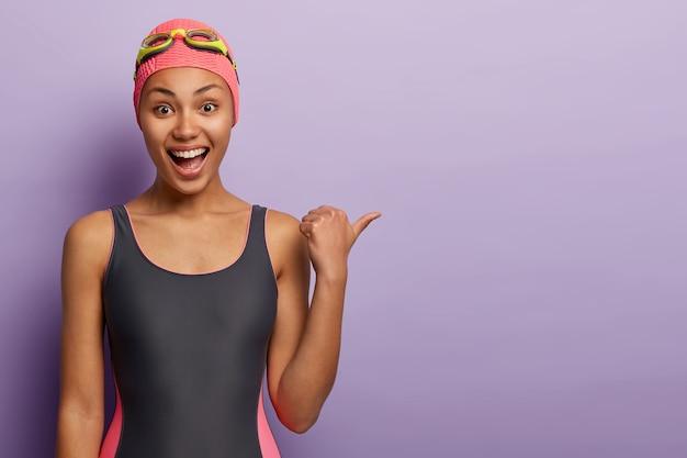 Vrolijke, donkere zwemster draagt een badmuts en een zwart zwempak