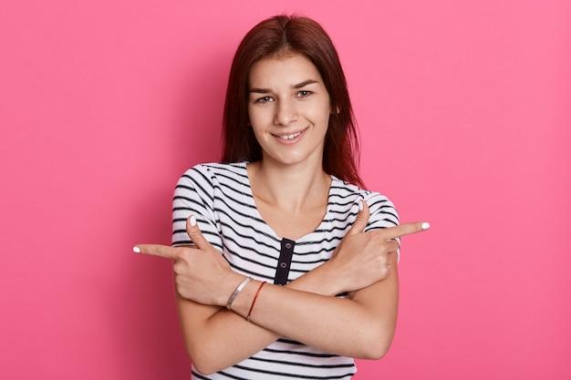 Vrolijke donkerharige vrouw kruist armen over borst, wijst naar links en rechts, geeft twee varianten, maakt reclame voor producten, vrouw staat tegen roze muur.