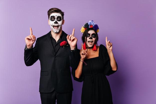 Vrolijke donkerogige jongen en meisje poseren emotioneel, vingers opdagen. schot van paar met gezichtskunst in mexicaanse stijl op paarse muur.