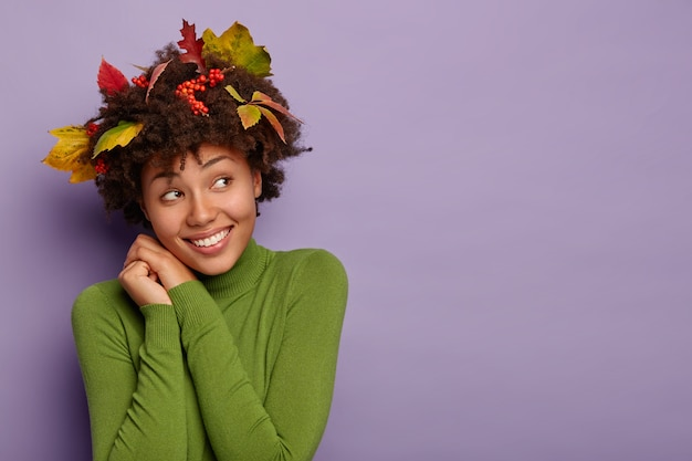 Vrolijke dromerige afro-amerikaans meisje kantelt hoofd, lacht aangenaam, kijkt opzij, maakt portret binnen, heeft gele bladeren, rowan bessen in haar