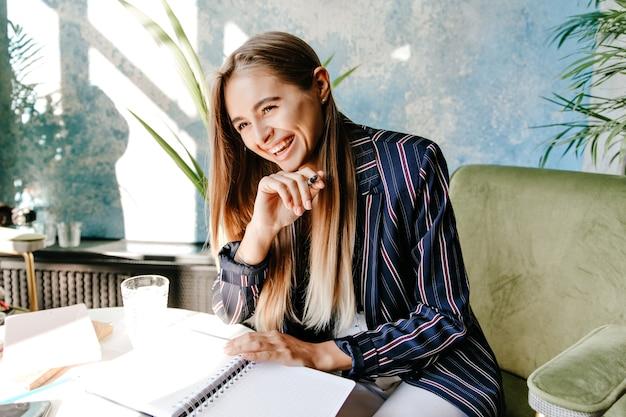 Vrolijke drukke dame lachen in café tijdens het werk. verbazend mooi meisje dat documenten met glimlach voorbereidt.