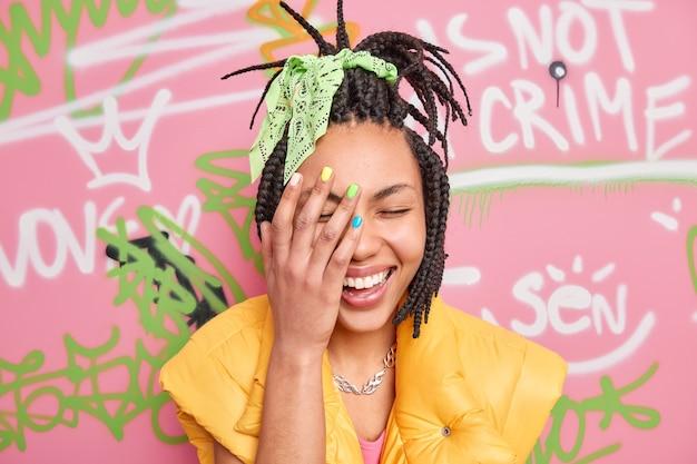 Vrolijke duizendjarige meisje lacht oprecht maakt gezicht palm voelt erg blij heeft trendy kapsel gekleed in vrijetijdskleding vormt tegen kleurrijke graffiti muur