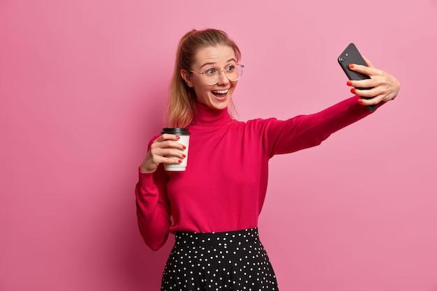 Vrolijke duizendjarige meisje neemt video op, neemt selfie op moderne smartphone, belt vriend via mobiele applicatie, drinkt koffie om mee te nemen, begint de dag met een verfrissend drankje