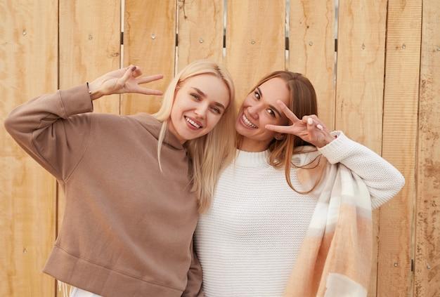 Vrolijke duizendjarige vriendinnen in trendy warme truien die vredestekens maken en kijken terwijl ze samen tegen een houten hek staan