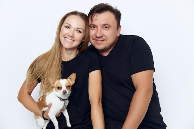 Vrolijke echtpaar knuffels zwarte t-shirts studio kleine hond in handen.