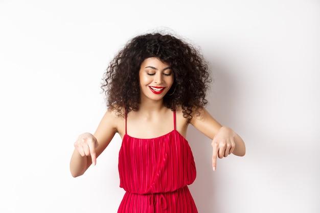 Vrolijke elegante vrouw in rode jurk en make-up, kijkt en wijst naar beneden met een tevreden glimlach, reclame tonen, staande op een witte achtergrond.