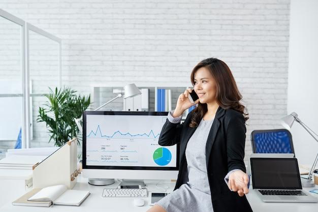 Vrolijke elegante zakenvrouw permanent op kantoor met grote monitor en praten over de telefoon met bu...