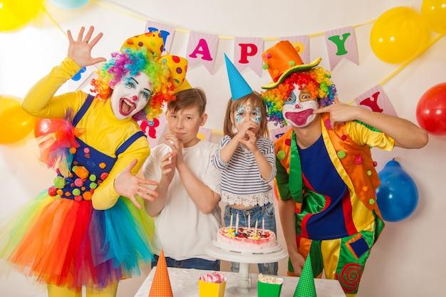 Vrolijke emotionele clowns op vakantie met kinderen blazen de taart uit
