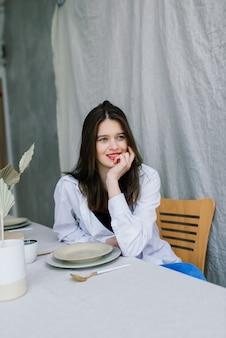 Vrolijke emotionele jonge vrouw zittend aan houten tafel met platen in de keuken thuis