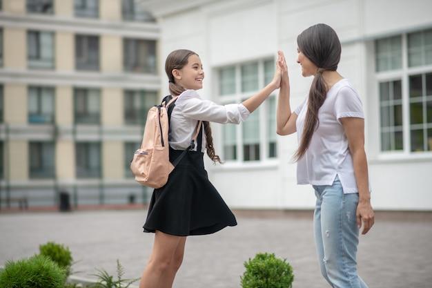Vrolijke emotionele moeder en dochter in schooluniform met rugzak ontmoetten elkaar na school.