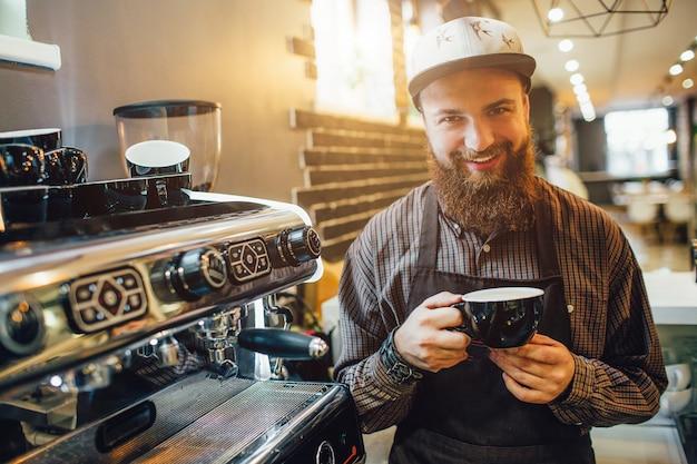 Vrolijke en bebaarde jonge man kijkt op camera en glimlacht. heholds achterbeker met koffie. guy staan op koffiemachine.