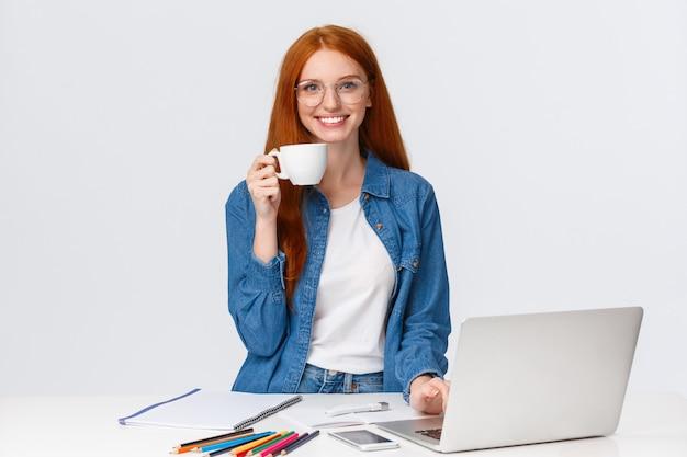 Vrolijke en energieke knappe roodharige vrouwelijke freelancer, drink te veel koffie glimlachend opgewonden en opgewonden, werkend via creatief cool project, met behulp van laptop, tekening, wit