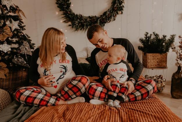 Vrolijke en gelukkige familie in pyjama's met kind liggen op het bed in de slaapkamer. familiekleding voor het nieuwe jaar ziet eruit als outfits. valentijnsdag viering geschenken
