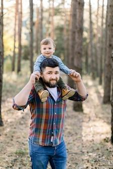 Vrolijke en gelukkige familie, knappe bebaarde vader en zijn zoontje schattige baby in de herfst park, spelen en lachen