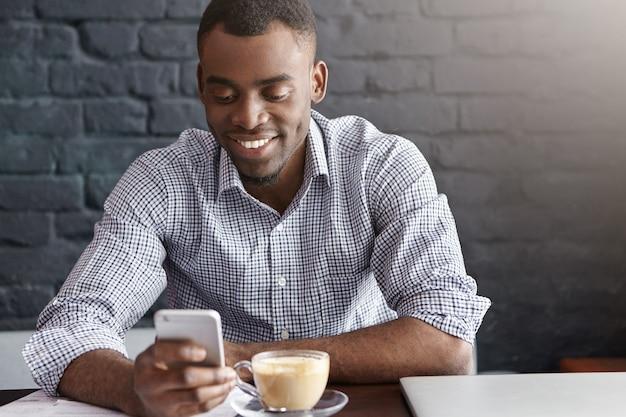 Vrolijke en gelukkige jonge donkere zakenman online berichten sturen