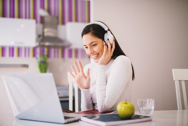 Vrolijke en gelukkige jonge vrouw zwaait naar een persoon met wie ze online studeert terwijl ze haar headset op heeft.