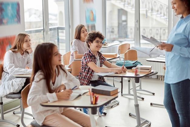 Vrolijke en gelukkige kinderen die aan bureau zitten terwijl leraar in schoolklas spreekt. basisschoolkinderen die op bureaus zitten.