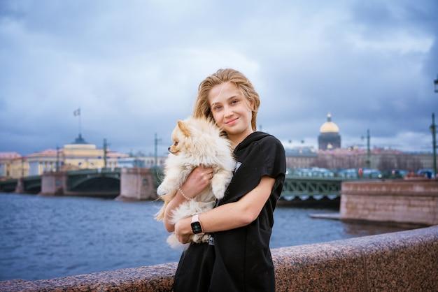 Vrolijke en gelukkige meisjestiener houdt en knuffelt pommeren spitz aan de kade in de stad op een bewolkte dag...