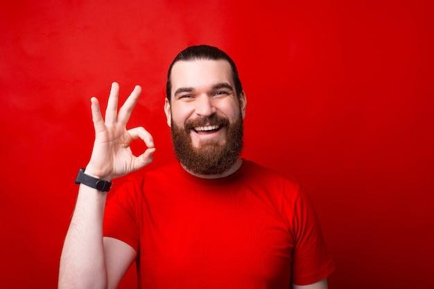Vrolijke en glimlachende bebaarde man die ok gebaar toont en zich op rood bevindt