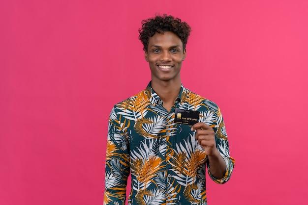 Vrolijke en glimlachende jonge knappe donkere man met krullend haar in een met bladeren bedrukt hemd terwijl hij zijn creditcard vasthoudt en toont