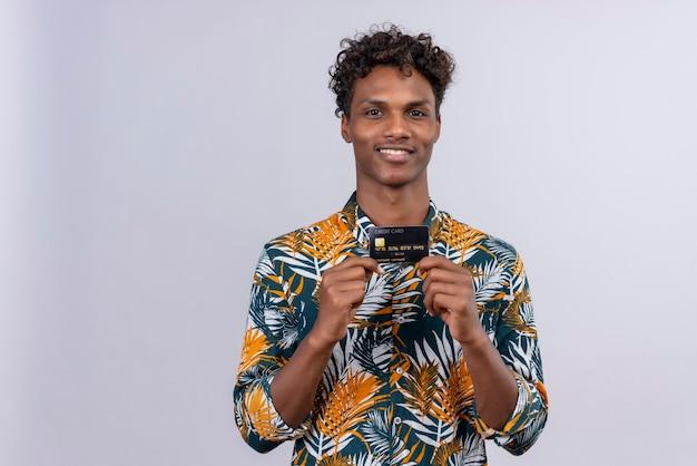 Vrolijke en glimlachende jonge knappe donkerhuidige man met krullend haar in bladeren bedrukt overhemd vasthouden en creditcard tonen