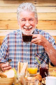 Vrolijke en grappige actieve aardige senior man die warme chocolademelk drinkt met baard en snor vies
