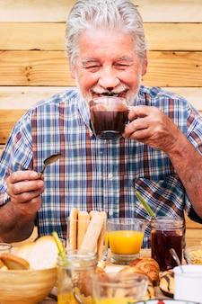 Vrolijke en grappige gelukkige mensen oude senior man die warme chocolademelk drinkt voor ontbijt thuis of hotel -concept van mooie oudere levensstijl voor jeugd oude blanke man met jonge geest