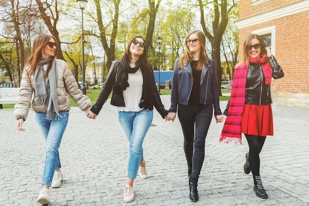 Vrolijke en mooie vrouwen lopen, hand in hand.