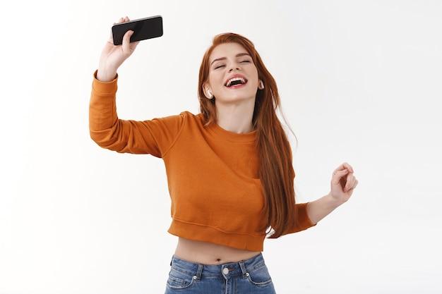 Vrolijke en ontspannen, zorgeloze roodharige hipster vrouw meegesleept met muziek, dansen hand opsteken met smartphone, meezingen met favoriete nummer luister playlist in draadloze koptelefoon, witte muur