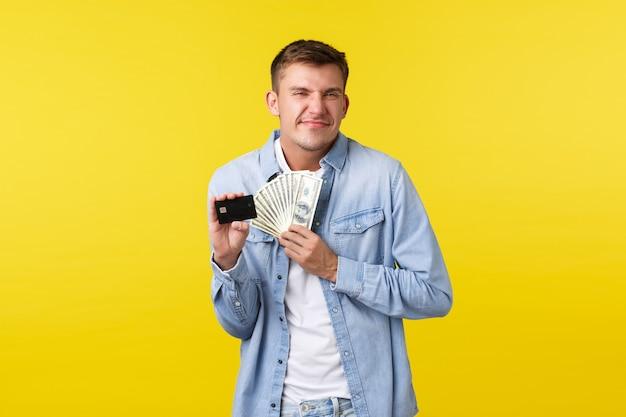 Vrolijke en opgetogen gelukkige blonde man die opgewonden kijkt, tevreden glimlacht als extra contante betaling ontvangt, creditcard met geld vasthoudt, gele achtergrond vrolijk staat.
