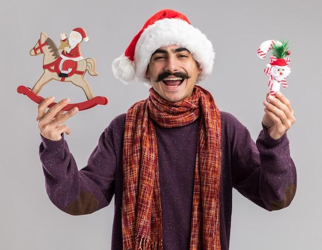 Vrolijke en opgewonden jonge besnorde man met een kerstmuts met warme sjaal om zijn nek met kerstspeelgoed met een glimlach op het gezicht over een witte muur
