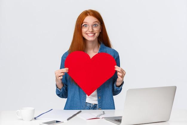 Vrolijke en opgewonden schattige vriendin met rood haar, kan niet wachten, geef grote rode valentijnskaarten hart aan vriend, sympathie tonen, verliefd bekennen