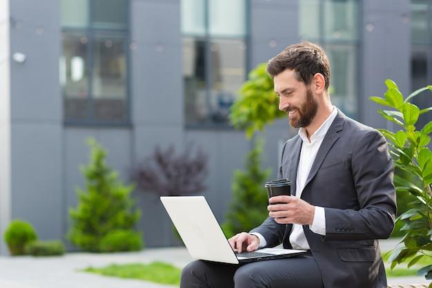 Vrolijke en succesvolle mannelijke zakenman die aan laptop werkt tijdens de lunch zittend op een bankje in de buurt van kantoor in pak en warme drank drinkend, bankier in de buurt van kantoor