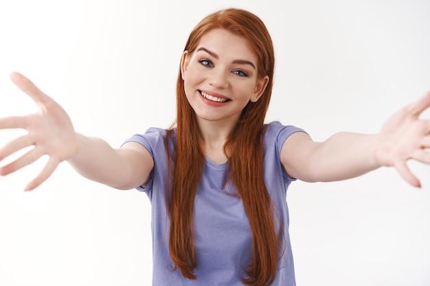 Vrolijke en tedere charmante roodharige vrouw met lang rood haar, strek handen naar voren om te knuffelen, wil iemand omhelzen of stevig vasthouden, glimlachend vriendelijke, witte muur