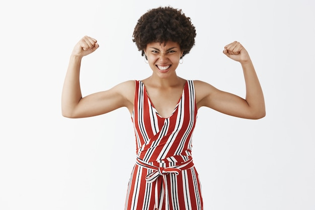 Vrolijke en tevreden knappe afro-amerikaan met krullend kapsel handen opsteken en spieren laten zien die over training gaan, gymresultaten met tevreden glimlach tonen