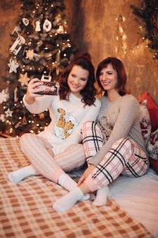 Vrolijke en vrolijke moeder en dochter in pyjama's selfie te nemen via mobiele telefoon zittend op bed tegen versierde kerstboom