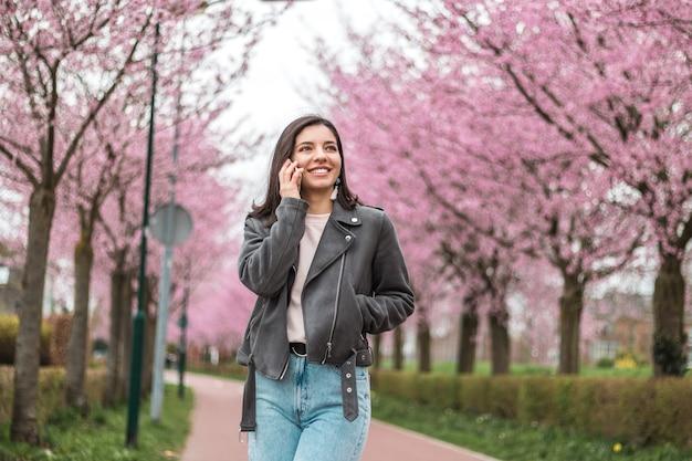 Vrolijke en zelfverzekerde jonge vrouw van gemengde rassen etniciteit aan de telefoon met geliefde vrienden of familieleden die alleen in bloeiend park met roze bomen lopen.