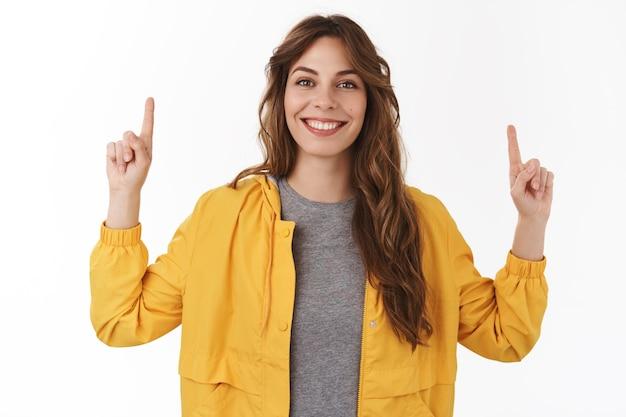 Vrolijke energieke knappe krullende europese vrouw die handen omhoog wijst en coole nieuwe promo laat zien die lacht, graag deelt interessante link aanbevelen probeer product richt de aandacht naar boven