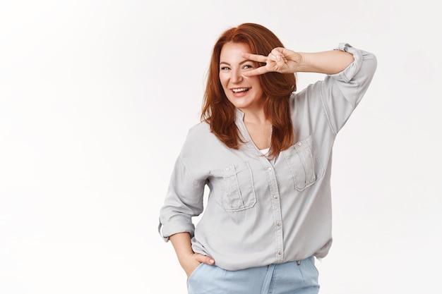 Vrolijke energieke knappe stijlvolle roodharige vrouw van middelbare leeftijd draag trendy blouse houd hand oog overwinning vredesgebaar glimlachend gelukkig witte muur