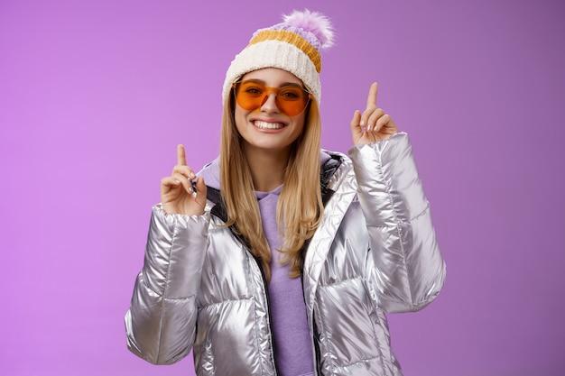 Vrolijke energieke vermaakte schattige blonde vrouw met plezier genieten van vakantie besneeuwde bergtocht met zonnebril
